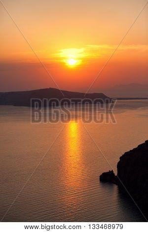 Sunset in Oia Santorini. The volcano caldera on background