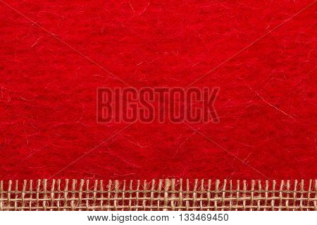 Border or frame formed by rough burlap rope mesh over red textile background.