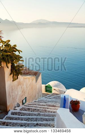 Street view in Oia Santorini. The sea and caldera on background. Shot at sunset