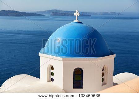 Blue dome church in Oia Santorini Greece. Sea and volcano on background. Horizontal shot