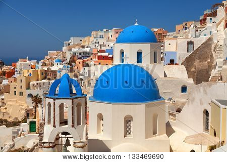 Landscape of Oia town in Santorini Greece with blue dome churches on foreground. Close up horizontal shot