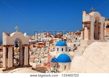 Landscape of Oia town Santorini. Three blue domed churches and two bell towers on foreground