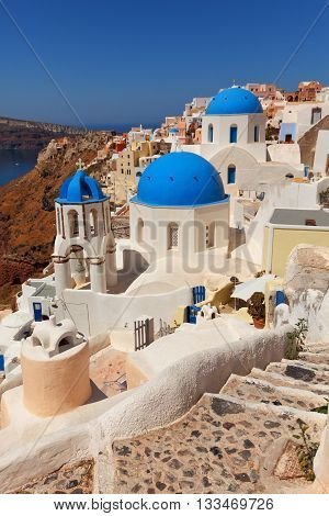 Landscape of Oia town in Santorini Greece with blue dome churches and stairs on foreground.