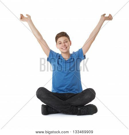 Cute teenager boy with stretching hands up in blue T-shirt and lotus posture over white isolated background