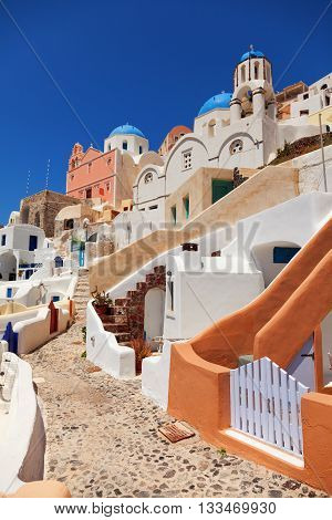 Typical Santorini street with houses and churches around