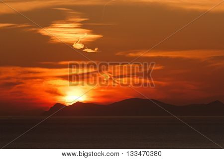 Sunset in Oia Santorini. Sun behind the volcano. Horizontal shot