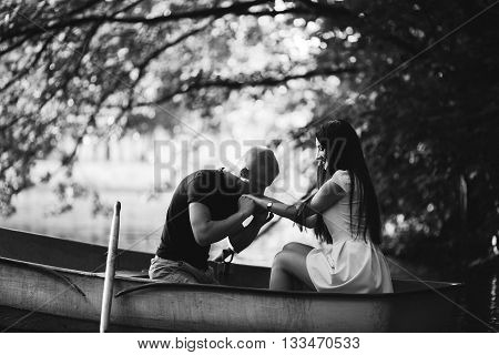 loving young couple enjoying in the boat, gently kisses the hand, blurred