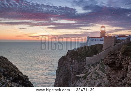 Magical sunset at sea with a view of the lighthouse in Sagres. Portugal.