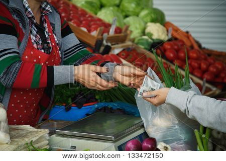 woman buys vegetables and herbs on the market summer day
