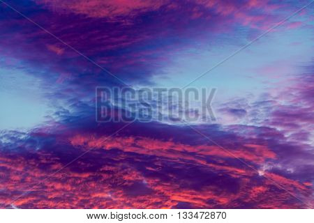 Romantic and dramatic cloud formation on dusk sky. blue and purple cold landscape with sunlight.