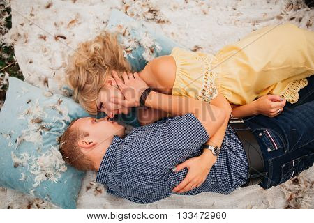 Happy couple playing with pillows loving couple man and woman lie on cushions in feathers