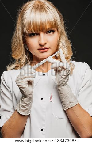 Nurse woman doctor in a white lab coat holding a scalpel