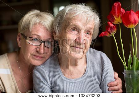 Woman sitting with her elderly mother.