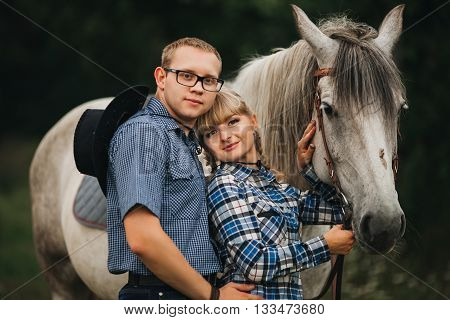 loving couple man and woman in a cowboy hat riding a horse