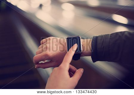Woman Using Smart Watch In Metro