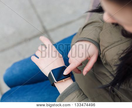 Hands Of A Girl Using Her Smart Watch Outdoors
