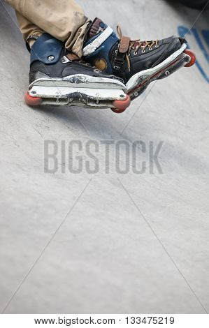 Feet of roller skater wearing aggressive inline skates sitting on a concrete ramp in outdoor skate park. Extreme sports athlete wearing roller skates for tricks and grinds