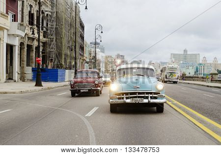 HAVANA - DECEMBER 10: American classic cars driving on the street on 10 December 2015 in Havana, Cuba. Brightly colored vintage American cars are very popular in Havana.