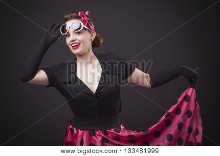 Happy smiling young woman with pin-up make-up and hairstyle posing on black background
