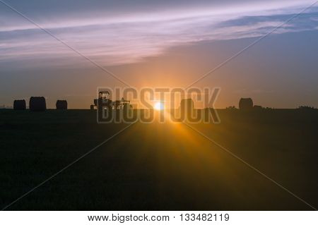 Farm tractor in field of large hay bales at sunset