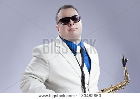 Music Concept and Ideas. Handsome Caucasian Musician with Alto Saxophone Posing in White Siut Against Gray. Horizontal Image