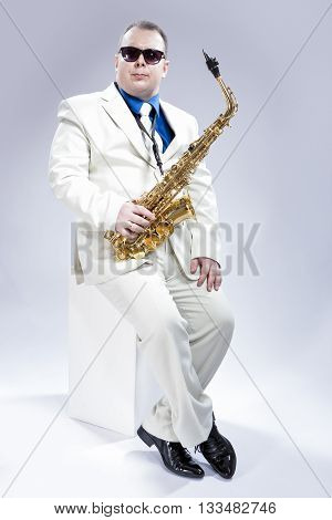 Music Concept and Ideas. Full Length Portrait of Caucasian Musician With Alto Saxophone Posing In White Suit and Black Sunglasses Against White Background. Vertical Image Orientation