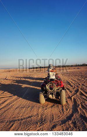 the girl in the desert on a Moto-Safari