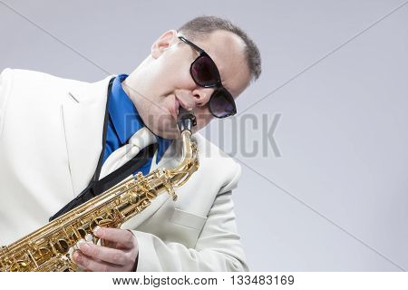 Music Concepts. Mature Musician Playing Alto Saxophone and Wearing Sunglasses. Posing in White suit Against White. Horizontal Image Orientation