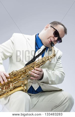 Caucasian Mature Male Musician Playing Alto Saxophone and Wearing Sunglasses. Posing in White suit Against White. Vertical Image Composition