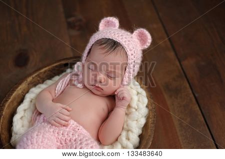 An overhead shot of a two week old newborn baby girl sleeping in a little wooden bowl. She is wearing a crocheted pink bear bonnet. Shot in the studio on a wood background.