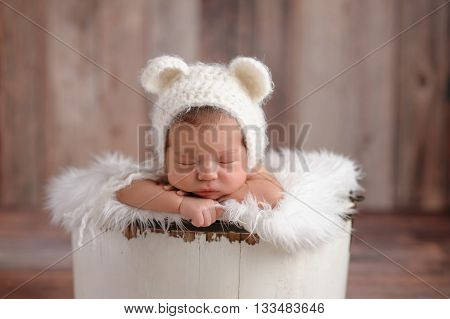 An 11 day old newborn baby girl sleeping in a little wooden bucket. She is wearing a crocheted white bear bonnet. Shot in the studio on a wood background.