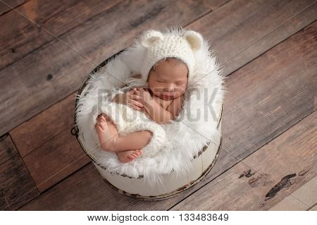 An overhead shot of an eleven day old newborn baby girl sleeping in a wooden bucket. She is wearing a crocheted white bear bonnet. Shot in the studio on a rustic wood background.