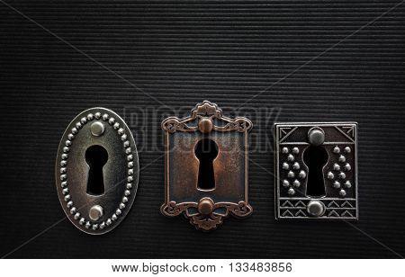 Three vintage locks on dark textured background