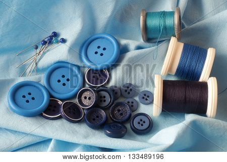 A collection of haberdashery items with a blue theme - buttons dressmaker's pins and cotton on bobbins. All on a piece of blue fabric.