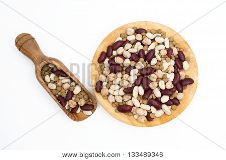 Legumes in wooden plate and scoop on white background.