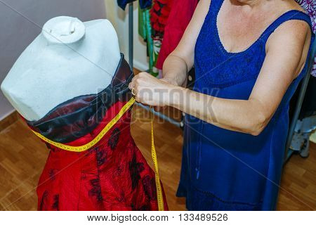 Close up of Seamstress doing arrangements in a dress.