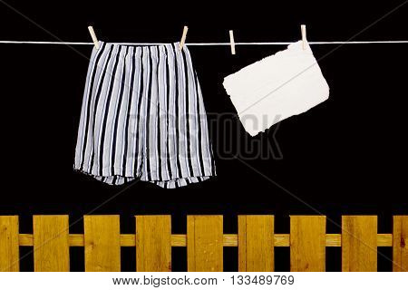 Men's underwear hanging on a clothesline over the fence
