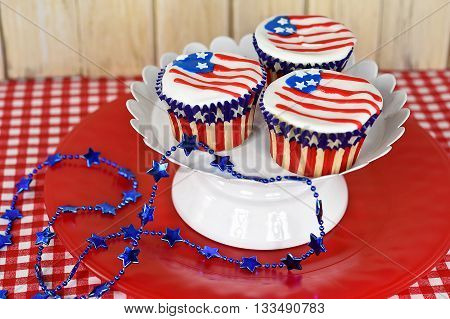 Flag icing on patriotic cupcakes with blue star necklace decoration.