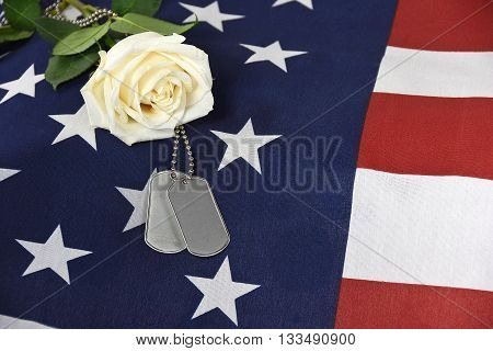 Single white rose and military dog tag on American flag.