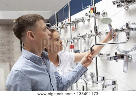 Couple shopping for bathroom equipment in hardware store, shop for construction