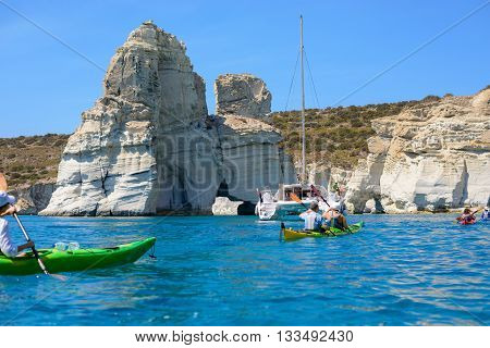 MELOS GREECE - SEPTEMBER 4 2012: A catamaran sailing boat and kayakers exploring Kleftiko. The caves and rock formations were used by pirates for hideouts.