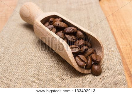 Heap Of Coffee Beans With Wooden Scoop On Jute Burlap On Table
