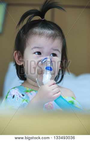 Cute asian child holds a mask vapor inhaler for treatment of asthma on sickbed in hospital. Breathing through a steam nebulizer. Concept of inhalation therapy apparatus. Vintage tone.