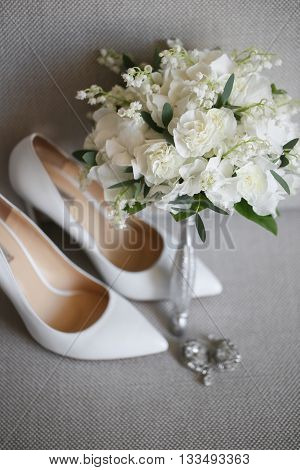 Bridal accessories: beige shoes and bride's . bouquet of white small flowers lily-of-the-valle