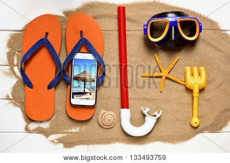 high-angle shot of a white wooden surface full of sand and some summer stuff, such a pair of flip-flops, a diving mask, a starfish or a smartphone with the picture of a beach taken by myself