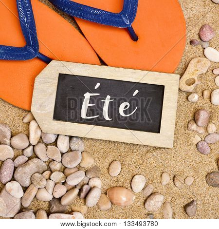 high-angle shot of a pair of orange flip-flops on the sand of a beach, a pile of pebbles and a rustic wooden label-shaped chalkboard with the word ete, summer in french, written in it