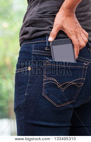 Smart phone in pocket of girl's jeans.