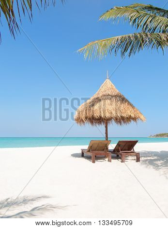 Wooden Deckchairs And Straw Parasol On Tropical Beach Palm Trees.