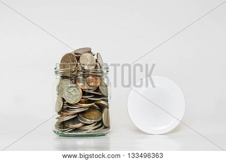 Coins in glass jar, and covered, with copy space on white background