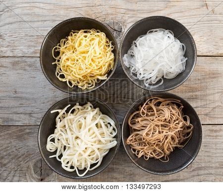 Different sorts of asian cooked noodles in bowls